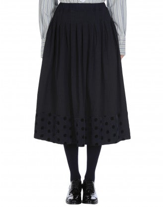 REVOLVE: Full, pleated skirt in plain navy with polka dot hem
